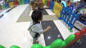 Bebé perdido que aprende caminar en piso de la alameda en medio de los compradores que el ` t del couldn cuida menos almacen de metraje de vídeo