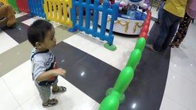Bebé perdido que aprende caminar en piso de la alameda en medio de los compradores que el ` t del couldn cuida menos metrajes