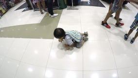 Bebé perdido que se arrastra en piso de la alameda en medio de los compradores que el ` t del couldn cuida menos almacen de metraje de vídeo