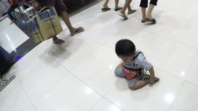 Bebé perdido que se arrastra en piso de la alameda en medio de los compradores que el ` t del couldn cuida menos metrajes