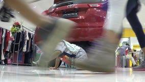 Bebé perdido que se arrastra en piso de la alameda en sitio de demostración de coche almacen de video