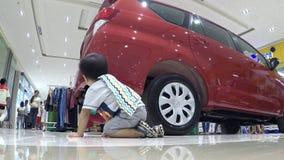 Bebé perdido que se arrastra en piso de la alameda en sitio de demostración de coche metrajes