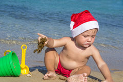 Bebé por el mar en un casquillo de Santa Claus Fotografía de archivo libre de regalías