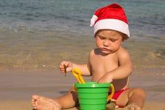 Bebé por el mar en un casquillo de Santa Claus Fotografía de archivo