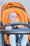 Bebé precioso al aire libre en cochecito anaranjado Imagenes de archivo