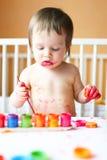 Bebé precioso con la pintura en casa Imagen de archivo