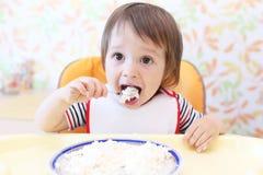 Bebé precioso que come el quark Imágenes de archivo libres de regalías