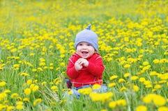 Bebé precioso sonriente contra prado de los dientes de león Imagen de archivo