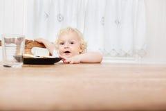 Bebé que alcanza para el alimento Imagen de archivo