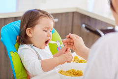 Bebé que alimenta con la cuchara en la cocina Imágenes de archivo libres de regalías