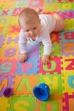 Bebé que aprende arrastrarse en la estera del alfabeto fotografía de archivo libre de regalías