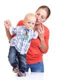 Bebé que aprende caminar con la ayuda de la madre Foto de archivo