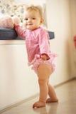 Bebé que aprende a de pé em casa Imagem de Stock