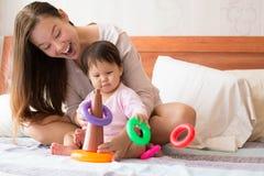 Bebé que aprende destrezas de la coordinación mientras que pone, y una madre orgullosa feliz que mira a su niño con júbilo imagen de archivo libre de regalías