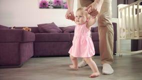 Bebé que aprende el paseo Niño que aprende recorrer El papá que detiene al niño y enseña a steping almacen de metraje de vídeo