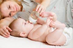 Bebé que bebe de la botella 5 meses de la muchacha Fotos de archivo libres de regalías