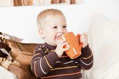 Bebé que bebe de um frasco e de um sorriso grandes foto de stock