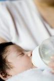 Bebé que bebe una botella Fotografía de archivo
