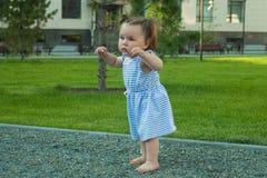 Bebé que camina por las piedras, prevención del pie plano en los niños que caminan en la superficie texturizada fotos de archivo