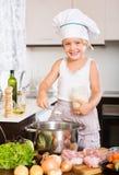 Bebé que cocina con la carne Imagen de archivo