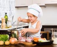 Bebé que cocina con la carne Fotos de archivo