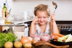 Bebé que cocina con la carne Fotografía de archivo
