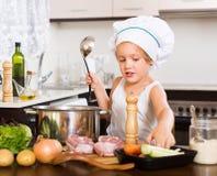 Bebé que cocina con la carne Foto de archivo