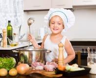 Bebé que cocina con la carne Imagenes de archivo