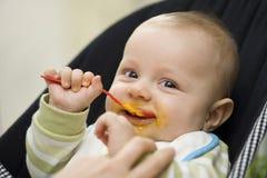Bebé que come con la cuchara Fotos de archivo