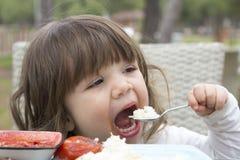 Bebé que come el arroz sin ayuda imagenes de archivo