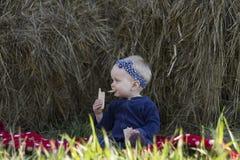 Bebé que come el pan quebradizo al aire libre Imagen de archivo