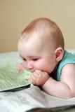 Bebé que come el periódico Imagen de archivo libre de regalías
