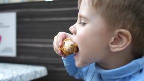 Bebé que come el pollo frito en un restaurante de los alimentos de preparación rápida, primer metrajes