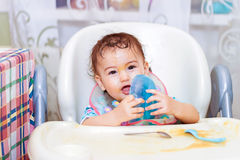 Bebé que come en la cocina en sittting en la tabla Fotografía de archivo