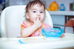 Bebé que come en la cocina en sittting en la tabla Fotografía de archivo libre de regalías