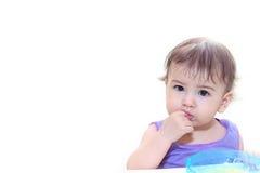 Bebé que come en la cocina en sittting en la tabla Imagen de archivo