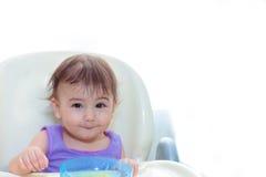 Bebé que come en la cocina en sittting en la tabla Imagen de archivo libre de regalías