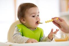 Bebé que come la comida con ayuda de la madre Imágenes de archivo libres de regalías