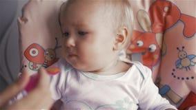 Bebé que come la comida en cocina con la mamá metrajes