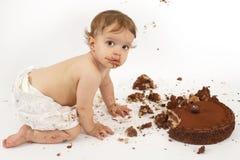 Bebé que come la torta de chocolate Fotografía de archivo libre de regalías