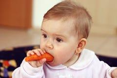 Bebé que come la zanahoria Foto de archivo libre de regalías