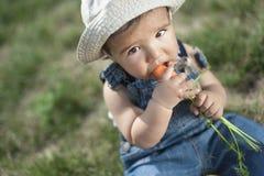 Bebé que come la zanahoria Fotos de archivo libres de regalías