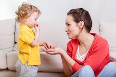 Bebé que come los bocados con la madre Imagen de archivo
