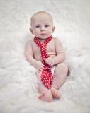 Bebé que desgasta el lazo rojo Foto de archivo