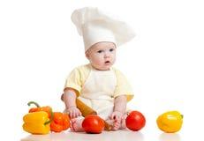 Bebé que desgasta un sombrero del cocinero con el alimento sano imágenes de archivo libres de regalías