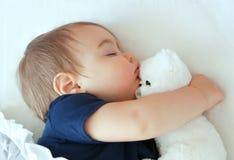 Bebé que duerme con el oso de peluche foto de archivo