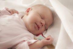 Bebé que duerme con una sonrisa fotos de archivo