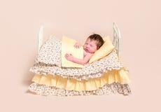 Bebé que duerme en cama con las hojas coloridas Foto de archivo libre de regalías
