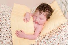 Bebé que duerme en cama con las hojas coloridas Imagenes de archivo