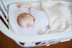 Bebé que duerme en el pesebre del co-durmiente atado a la cama de los padres foto de archivo libre de regalías